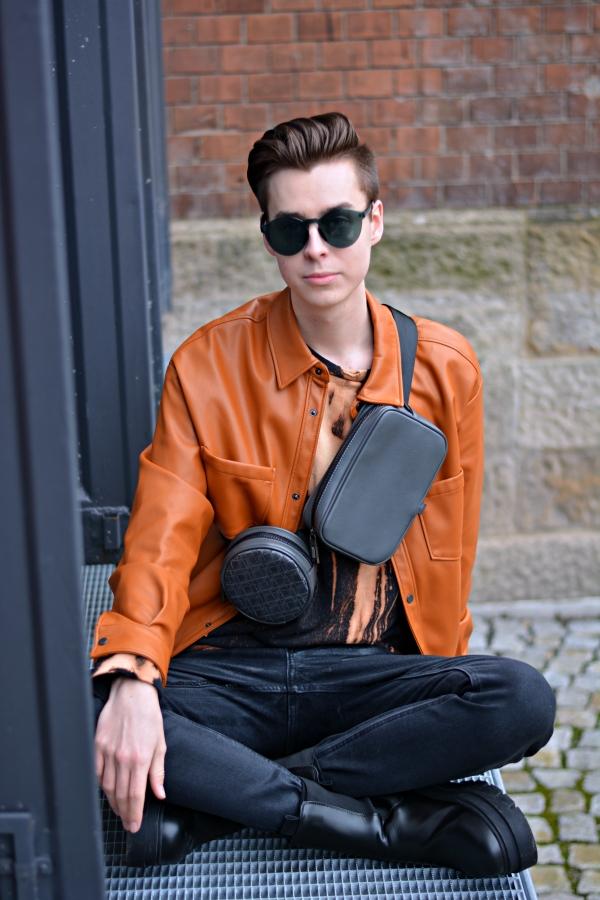 Modeblogger sitzend auf Metallplattform. Im Hintergrund Backsteine.