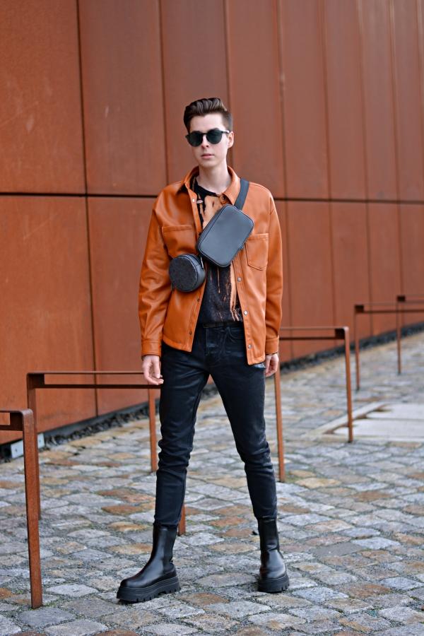 Modeblogger vor rostiger Wand in Overshirt in orange, mit grauer Bauchtasche und schwarzen Boots