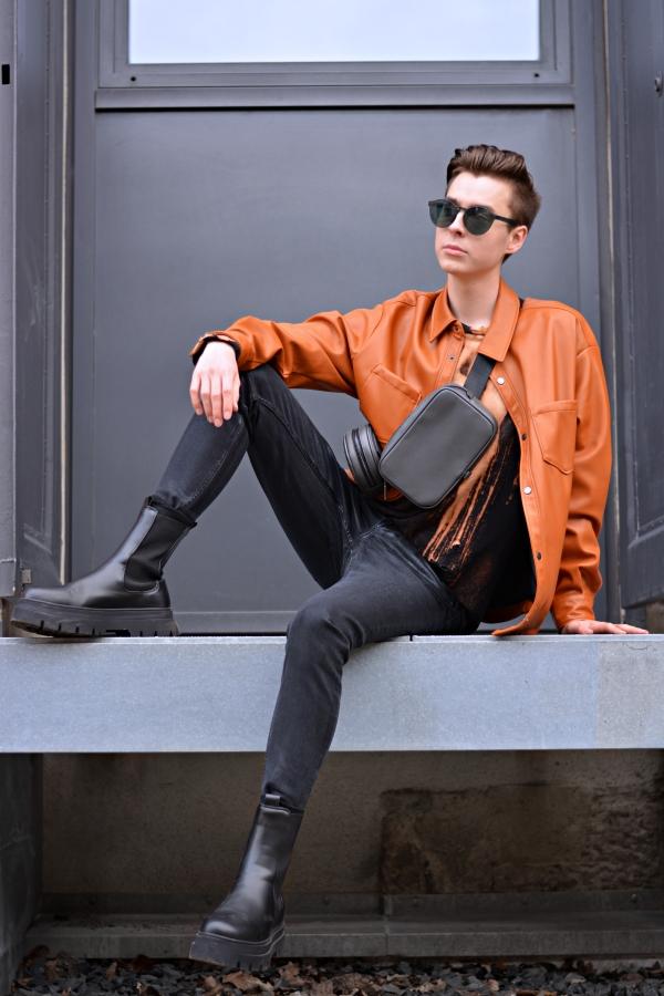 Junger Modeblogger sitzt auf Metallplattform. Er hat ein Overshirt in orange an und Boots