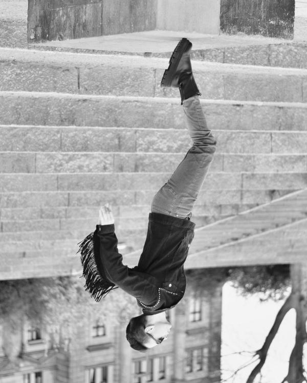 schwarz weiß Foto, welches auf dem Kopf steht. Junger Mann steht auf Zehnspitzen, Fransen seiner Jacke fliegen.