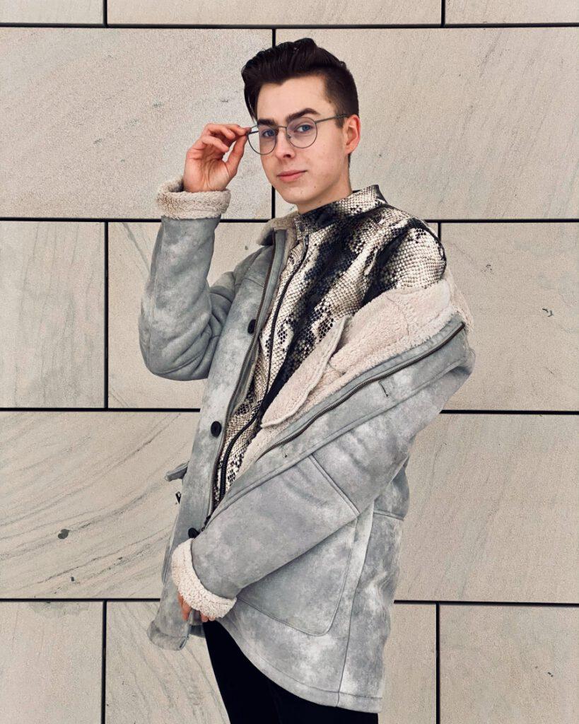 pierrefekt mit Brille, Schlangenlederjacke und Mantel
