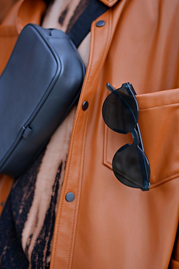 Detailfoto von Overshirt in orange, Bauchtasche in grau und Sonnenbrille