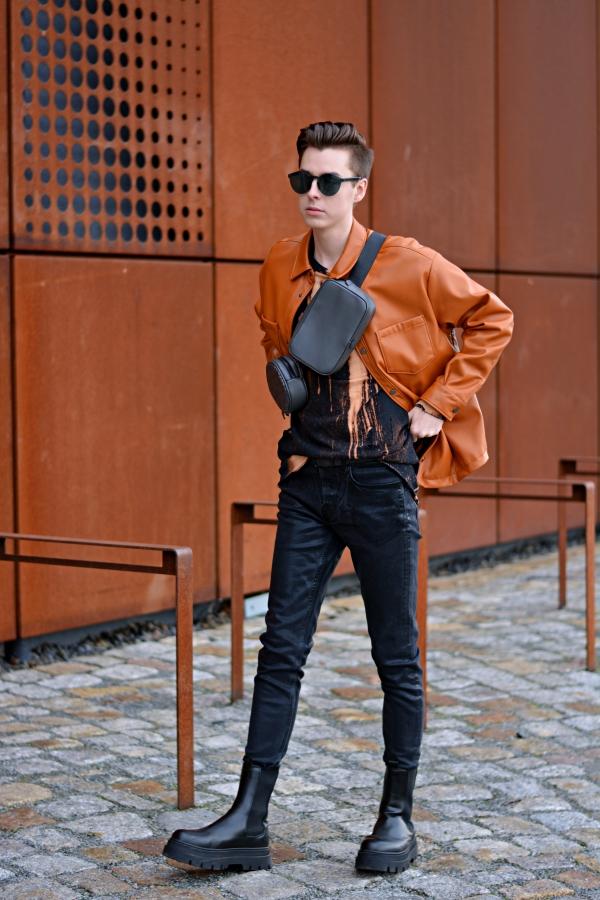Modeblogger vor rostiger Kulisse. Overshirt in Orange. Schwarze Hose und Boots. Pullover in schwarz/orange