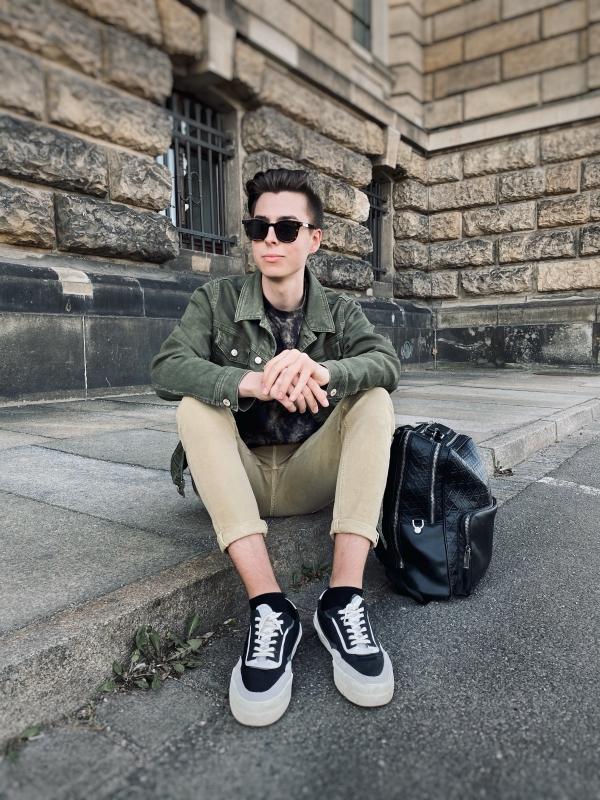 Modeblogger sitzt auf Boden. Grüne Jeansjacke und Hose in Sand.