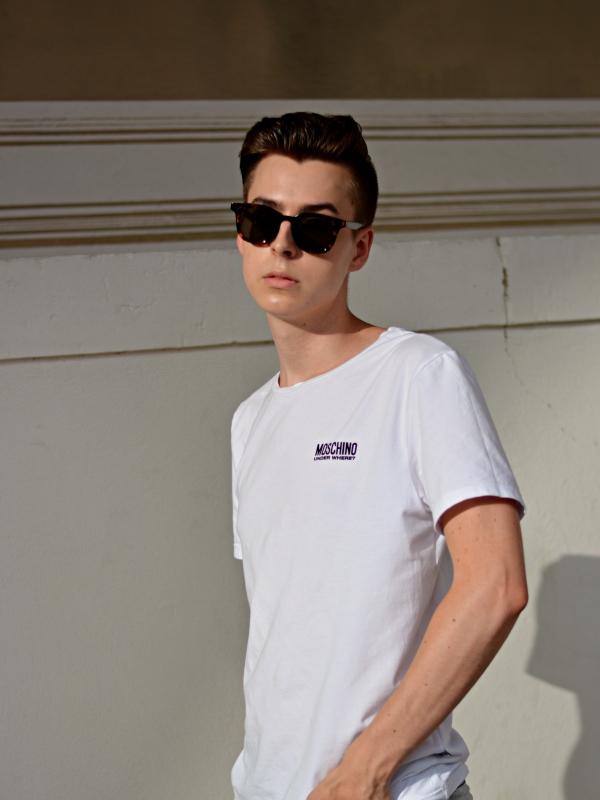 Modeblogger mit dunkler Sonnenbrille schaut in die Kamera. Eine Brille kann auch schon ein Sonnenschutz sein.