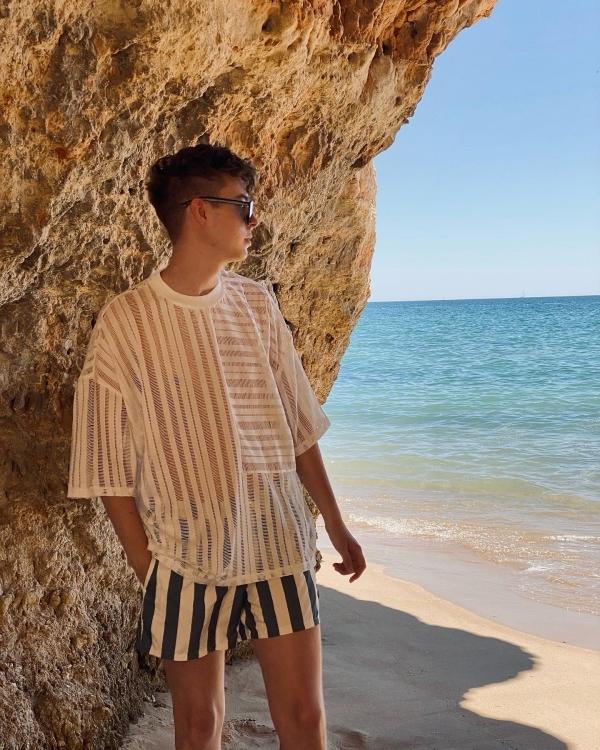weißes Netzshirt und blau/weiße Badehose vor Felsen und Meer