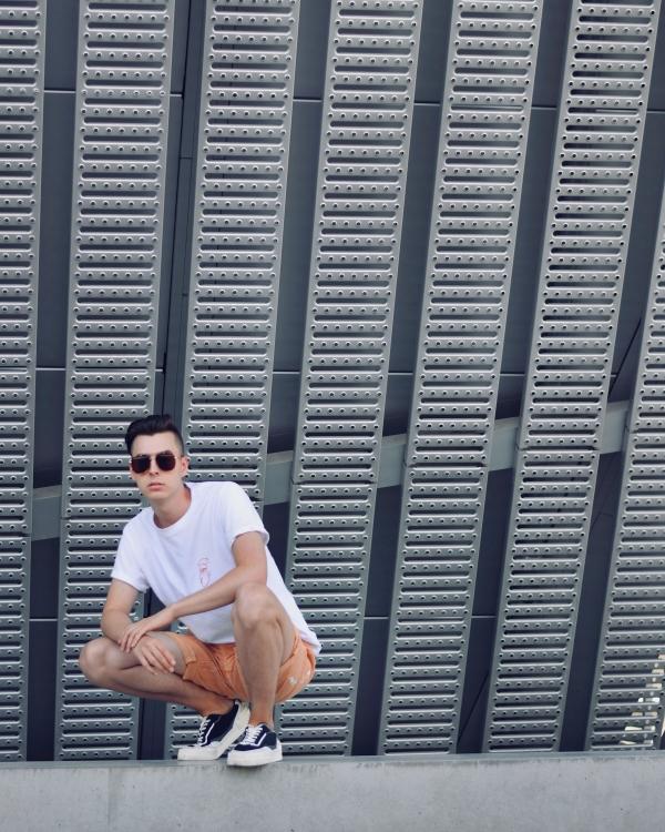 Modeblogger hockt vor grauer Wand