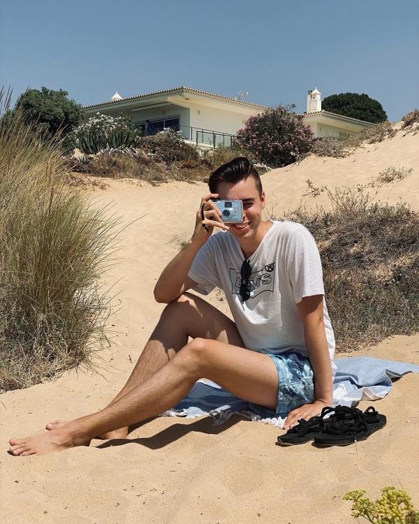 Pierre Engelmann am Strand mit Einwegkamera in der Hand