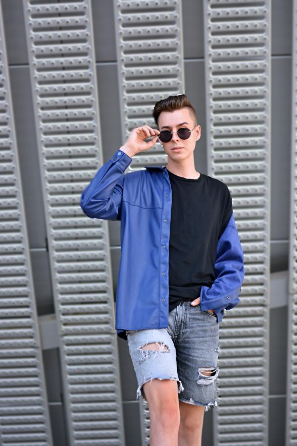 Fashionblogger vor grauem Hintergrund mit blauer Lederjacke